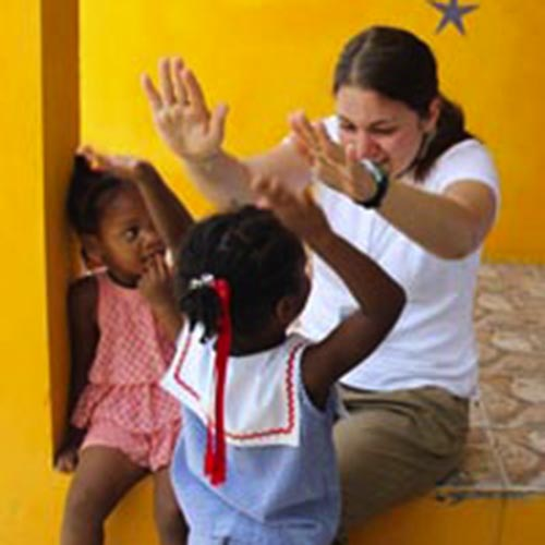 Student playing with children in Barbados